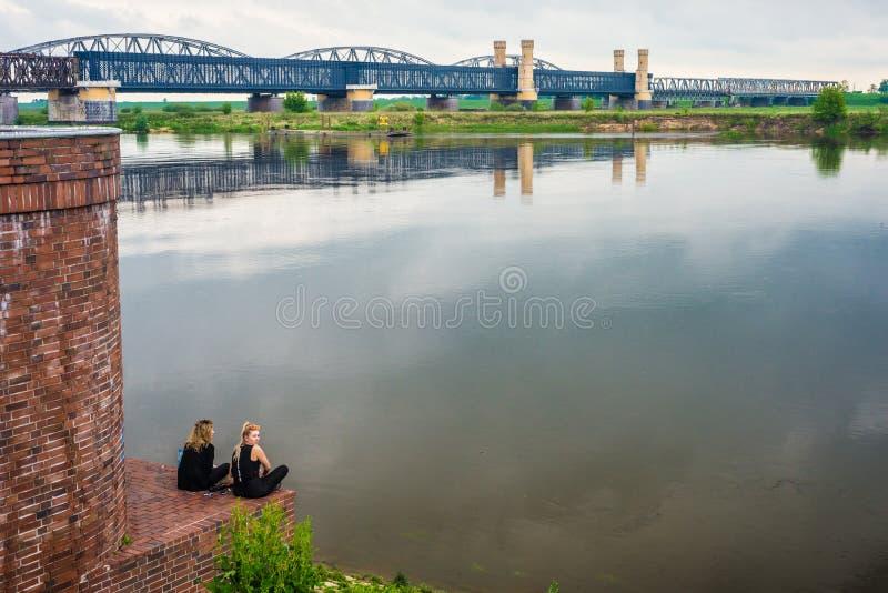 老钢铁路桥在特切夫和两个女孩坐 图库摄影