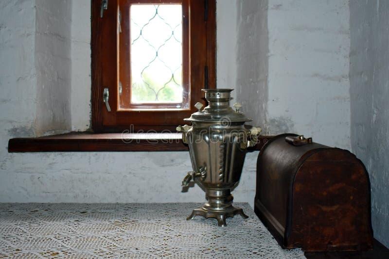 老铜俄国式茶炊和木胸口在窗口在屋子里 库存照片