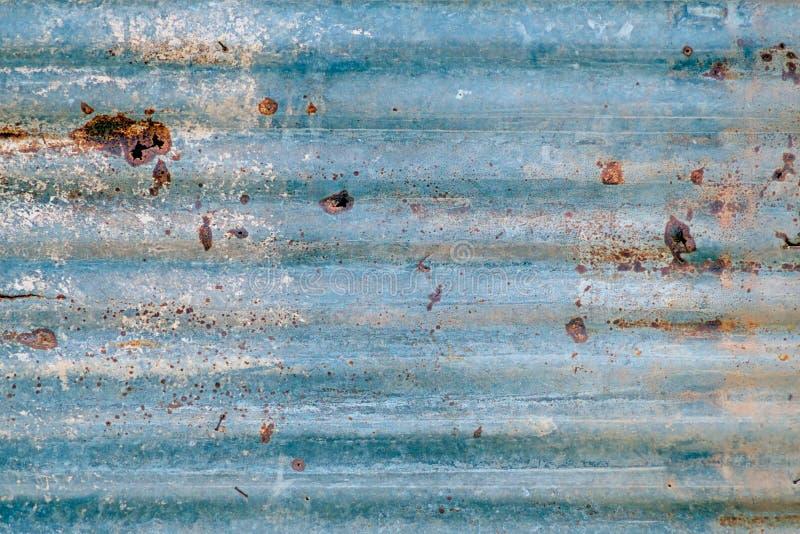 老锌屋顶,蓝色生锈的金属墙壁 图库摄影
