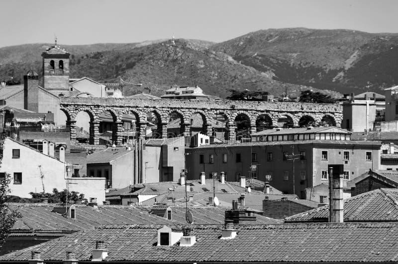 老镇塞戈维亚,有多雪的山和老渡槽的西班牙鸟瞰图  黑色白色 免版税库存照片