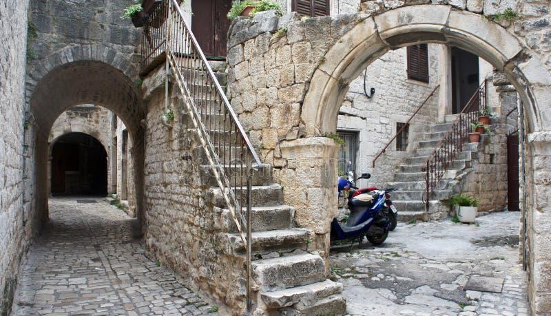 老镇狭窄的街道的石房子,与archs的美好的建筑学和台阶,特罗吉尔,达尔马提亚,克罗地亚 图库摄影