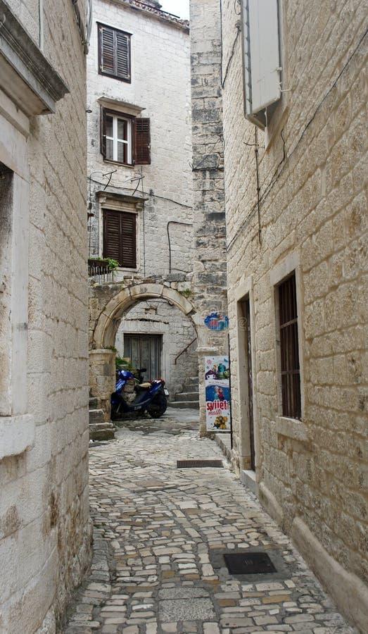 老镇,与曲拱的美好的建筑学,好日子,特罗吉尔,达尔马提亚,克罗地亚狭窄的街道的石房子  库存照片