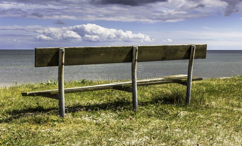 老长木凳有在海洋的好的看法 免版税库存照片