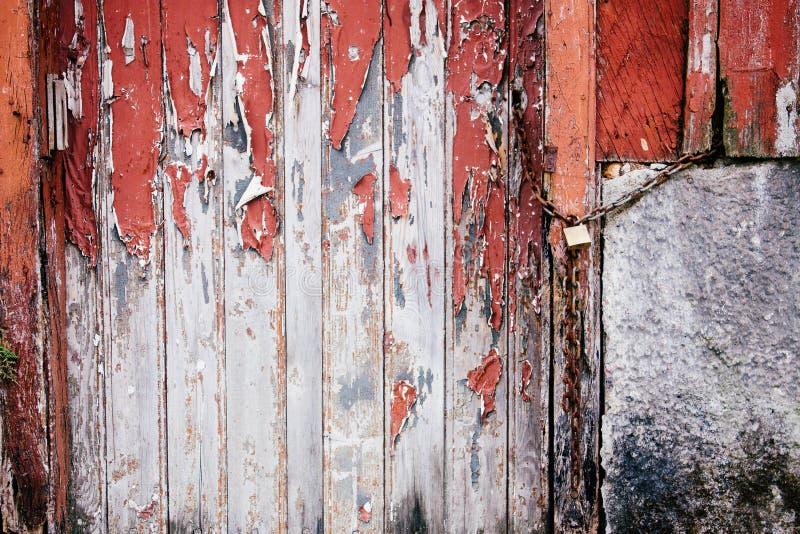 老难看的东西和被风化的红色和白色木锁着的门与生锈的链子 免版税库存图片