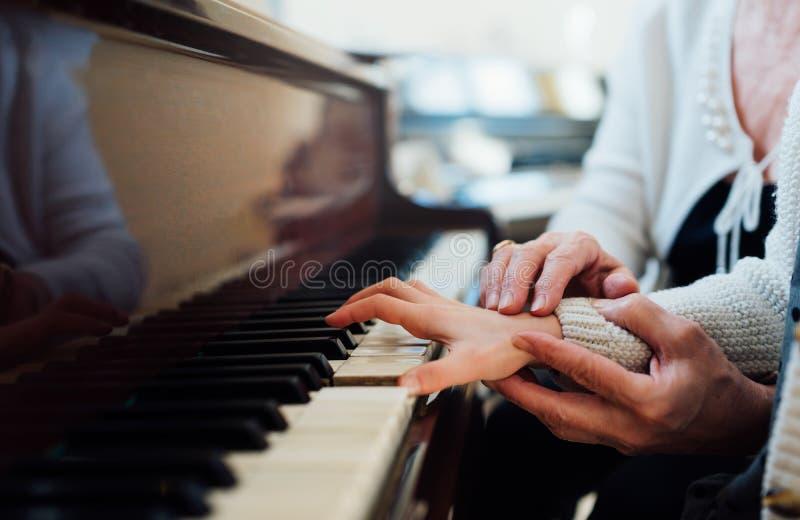 老音乐教师的老练的手帮助儿童学生 免版税库存图片