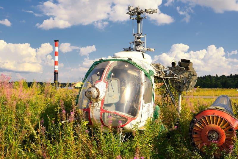 老飞机机体和生锈的直升机在绿草 免版税图库摄影