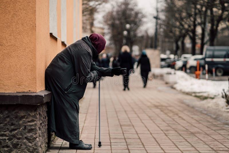 老饥饿的无家可归的女性叫化子照片乞求为施舍和在街道 库存图片