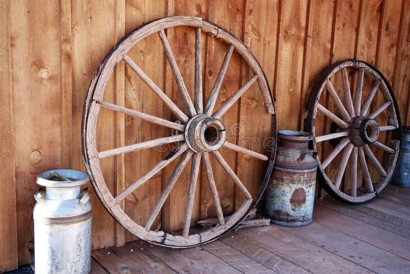 老马车车轮和牛奶罐头在农场 免版税图库摄影
