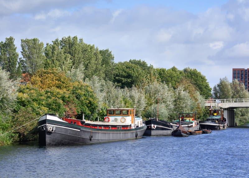 老驳船在有绿色植被的,提耳堡大学,荷兰一条运河停泊了 免版税图库摄影