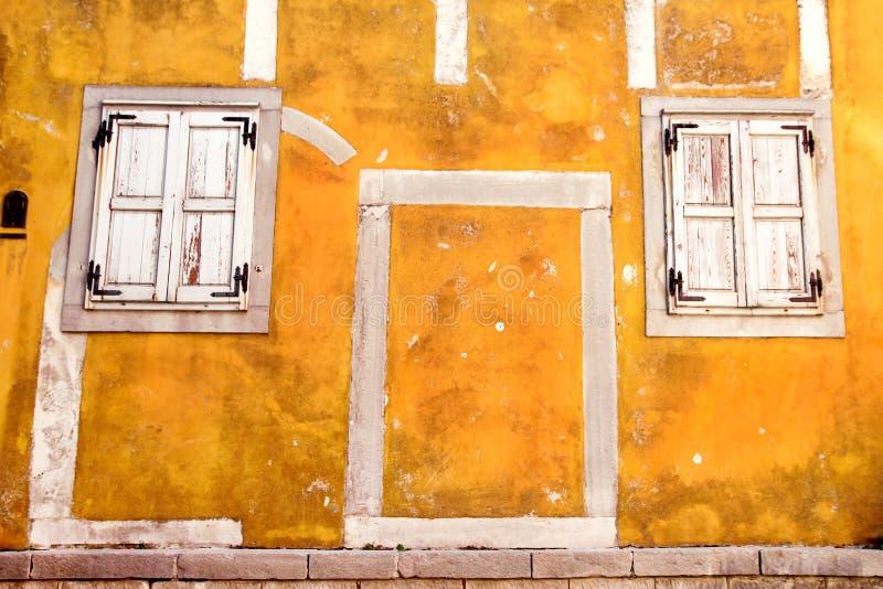 老黄色在黄色混凝土建筑/建筑背景的门面/经典葡萄酒木窗口 库存图片