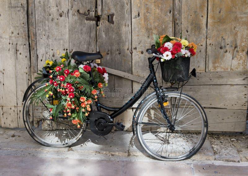 老黑自行车把变成花显示在马泰拉,意大利 库存图片