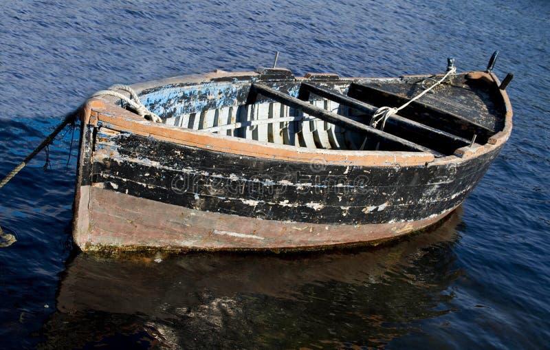 老黑色小船捕鱼 免版税库存图片