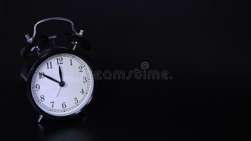 老黑葡萄酒闹钟的接近的图象 十分钟在12点前 库存照片