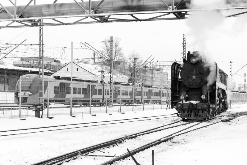 老黑蒸汽机车在俄罗斯在现代电车背景的冬天  免版税库存图片