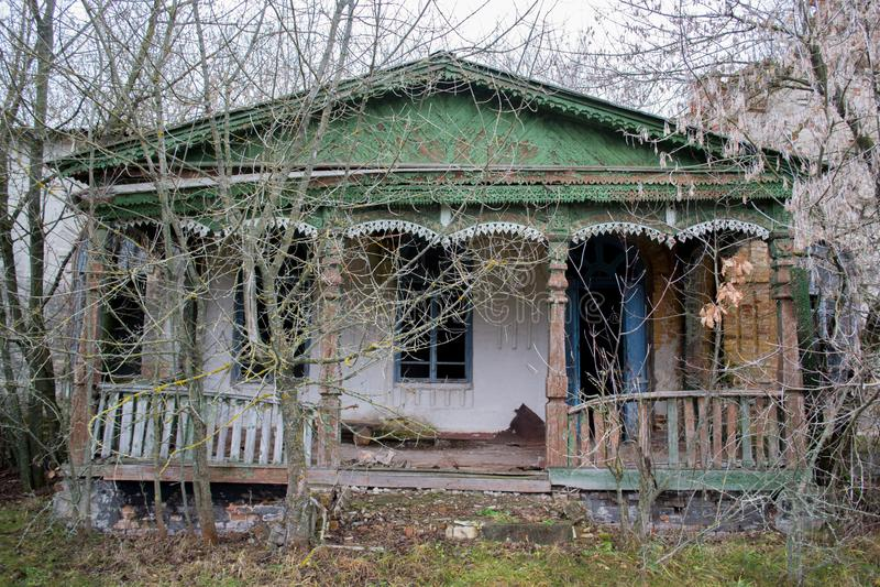 老,被忽略的,高傲的房子和门廊在树中 绿色老破裂的木头纹理被绘 免版税库存图片