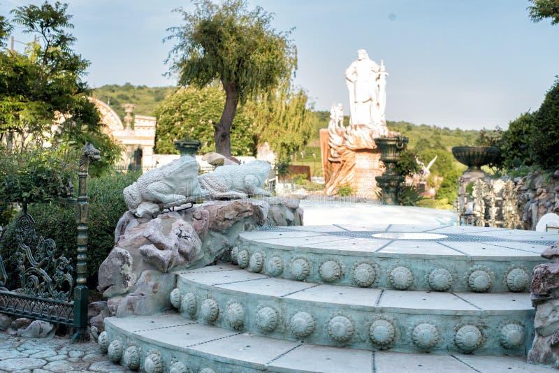 老巴洛克式的台阶,户外 台阶由石头制成 胡同在有花的美丽的庭院里和树和青蛙 图库摄影