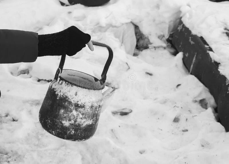 老水壶在贫寒的手上 免版税库存照片
