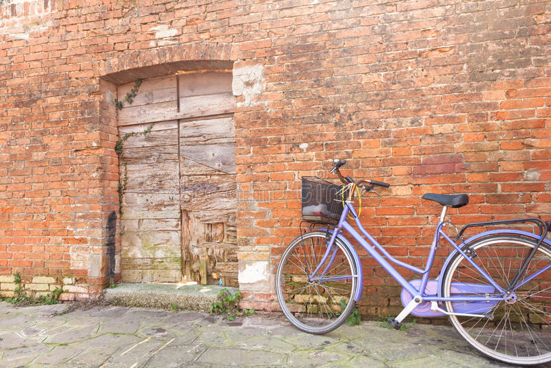 老紫罗兰色自行车在Burano海岛长期停放了外在墙壁 图库摄影