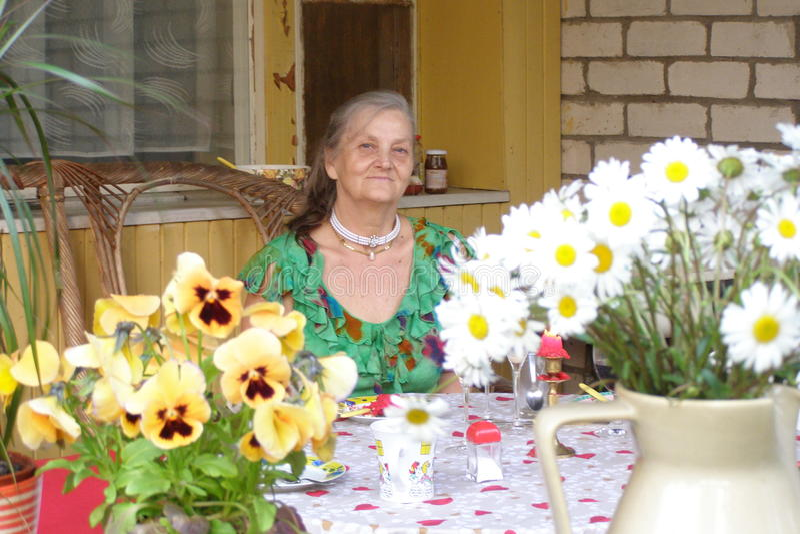 老年迈的妇女,大阳台,乡间别墅,春黄菊 图库摄影
