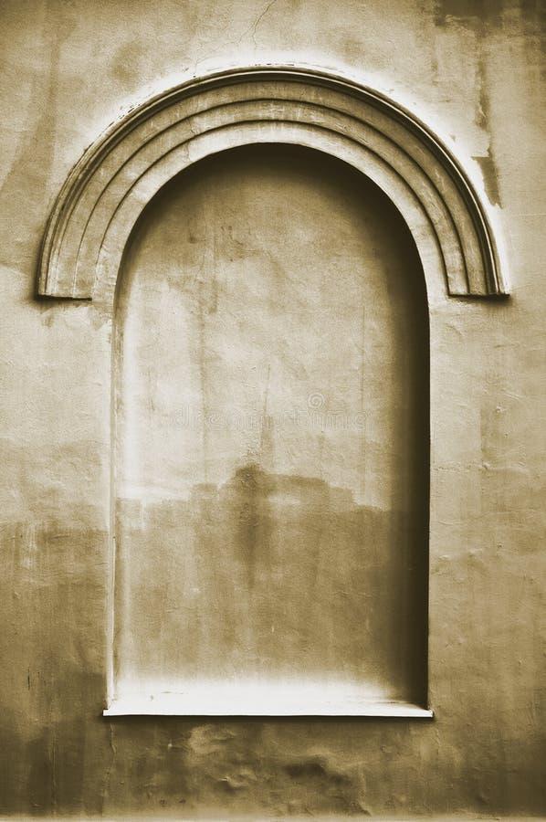 老年迈的涂灰泥的虚假曲拱错误假窗口灰泥框架背景拷贝空间,黑暗的垂直的米黄乌贼属纹理 免版税图库摄影