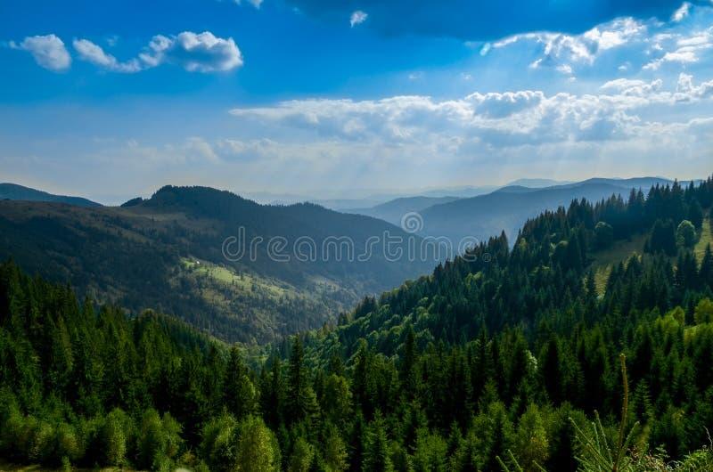 老farmer';s木房子在大象山站立在干草堆附近反对山峰背景  库存照片