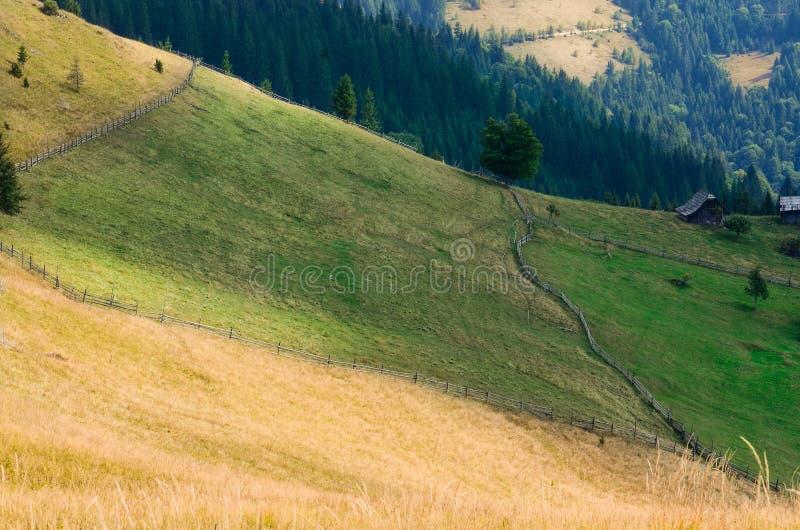 老farmer';s木房子在大象山站立在干草堆附近反对山峰背景  免版税库存照片