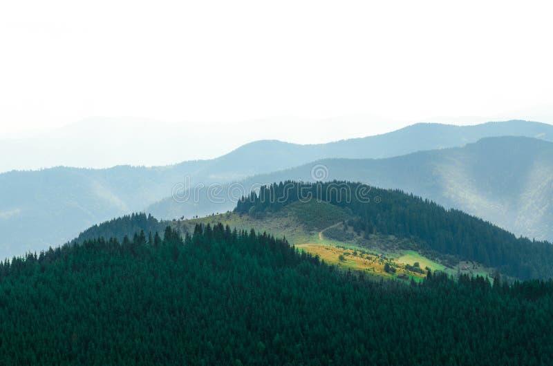 老farmer';s木房子在大象山站立在干草堆附近反对山峰背景  库存图片