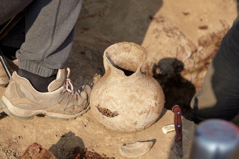 考古学塞浦路斯挖掘kato paphos公园 被找到的人工制品,变老了在地面上的损坏的陶瓷瓶子 真正的挖掘机的过程 两位考古学家的腿 库存照片