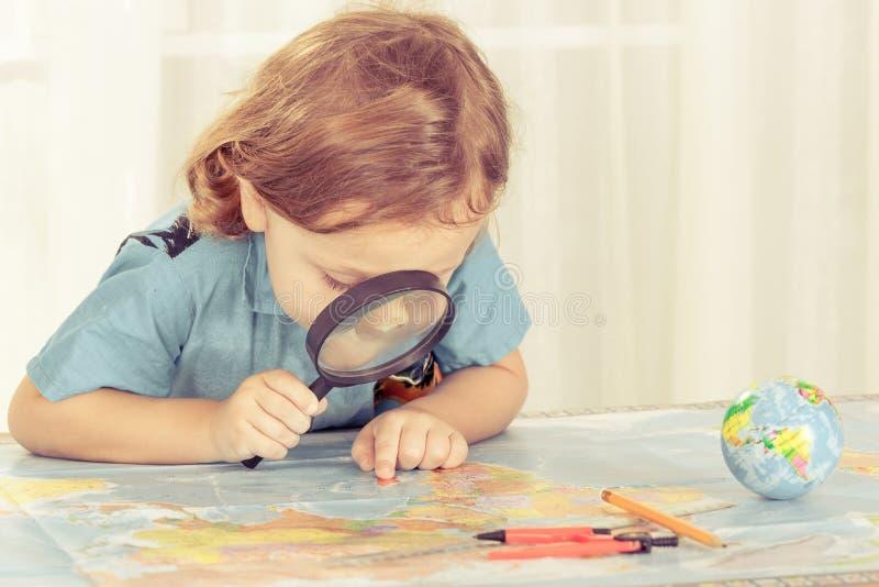考虑与放大镜的小男孩一张世界地图 图库摄影