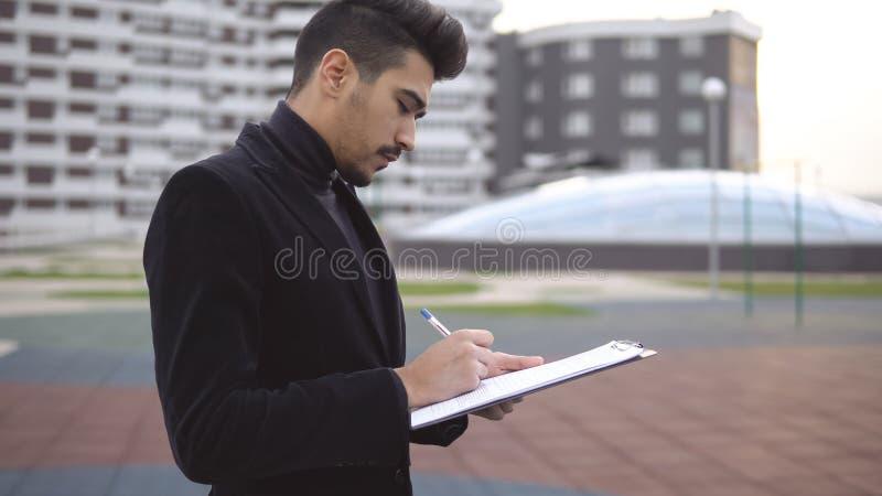考虑与笔和纸文件夹的新产品想法的年轻企业主 免版税库存照片