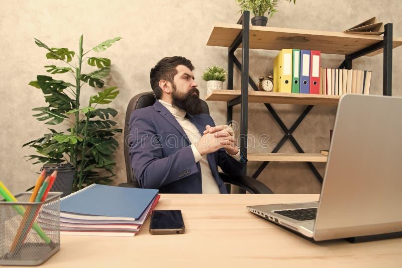 考虑主要目标 人有胡子的上司坐有膝上型计算机的办公室 解决业务问题的经理 ?? 库存图片