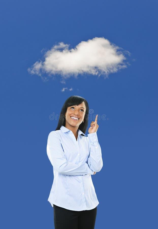 指向云彩的微笑的少妇 免版税库存照片