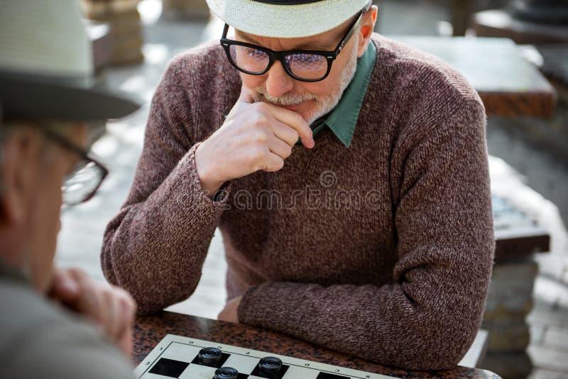 考虑在验查员的接下来的步骤的成熟男性领抚恤金者 免版税库存照片