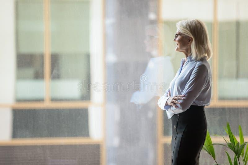 考虑战略的确信的成熟女实业家,站立在窗口附近 库存图片