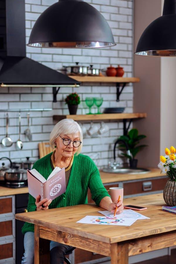 考虑早期梵文的桌的可爱的年迈的女性坐在厨房用桌上 库存照片