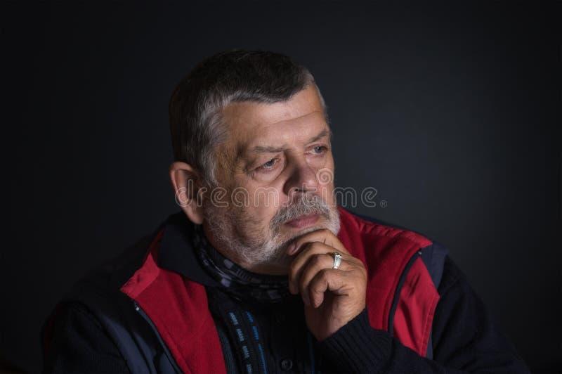 考虑生活问题的老人画象 免版税图库摄影