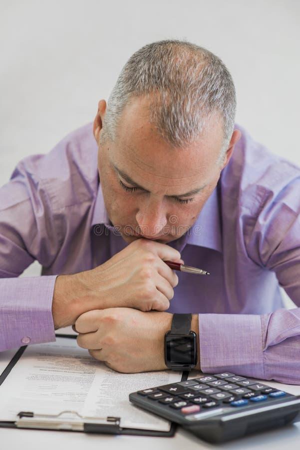 考虑税的企业人 征税概念 坐在办公室的年轻沮丧的商人照片  免版税库存照片