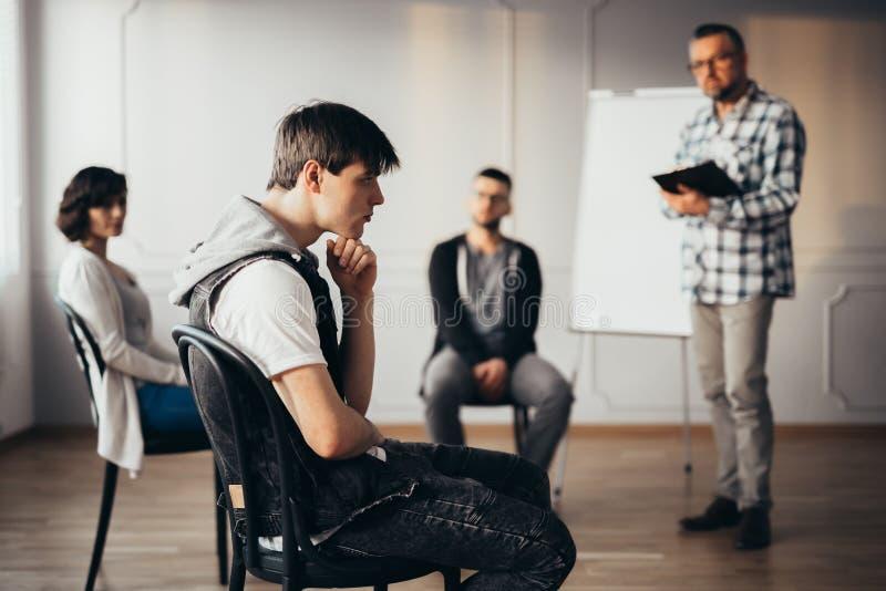 考虑answear的年轻人在小组教练的会议期间 免版税库存照片