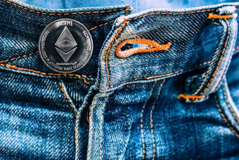 而不是按钮的ETH硬币在牛仔裤 库存照片