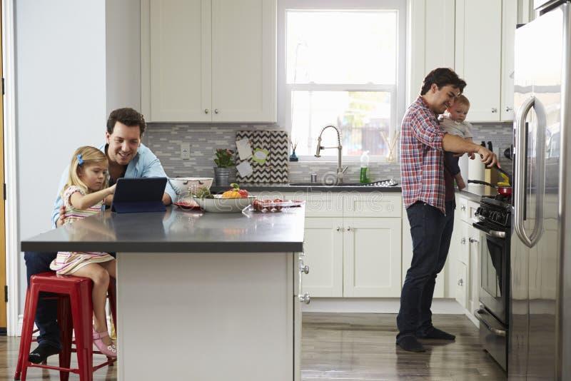 而其他爸爸烹调,女孩在有爸爸的厨房使用片剂 图库摄影
