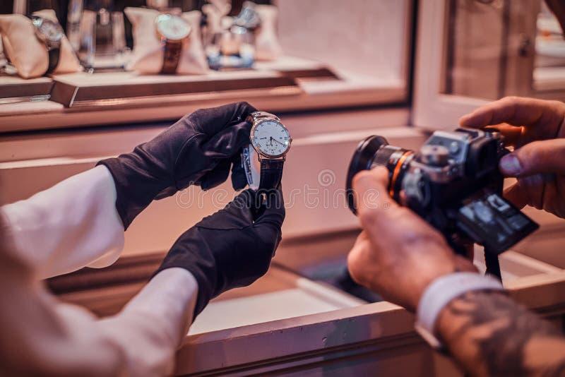 而售货员拿着他们,Tattoed摄影师是昂贵的手表照相在毫华商店 免版税库存照片