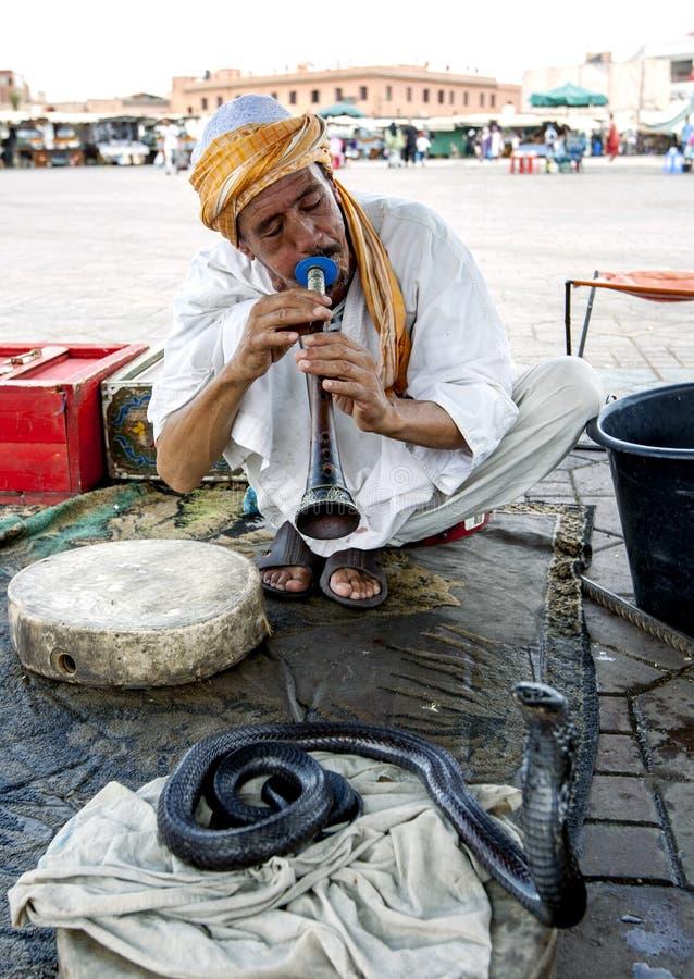 耍蛇者在Djemaa elFna,大广场演奏他的往一条眼镜蛇的长笛在马拉喀什麦地那在摩洛哥 图库摄影
