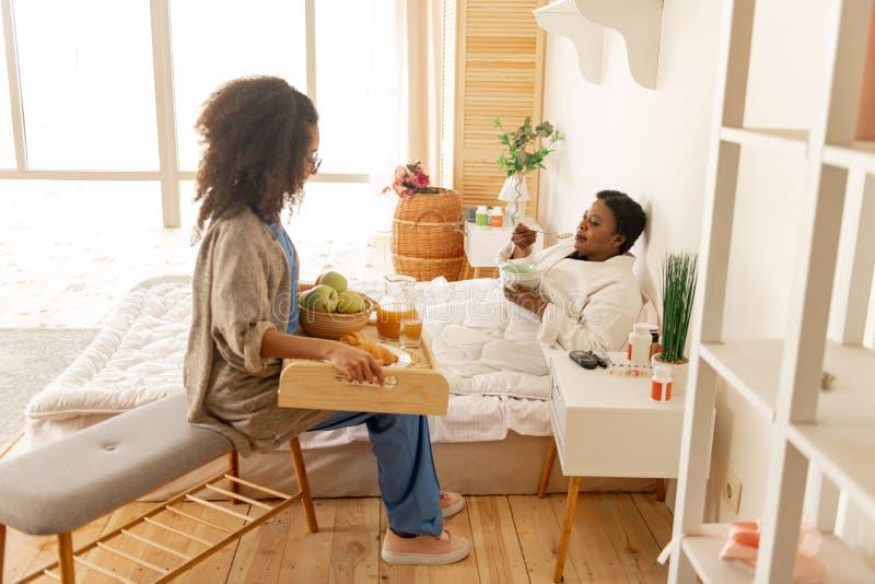 耐心在床上和享用谈话的早餐护理 免版税图库摄影