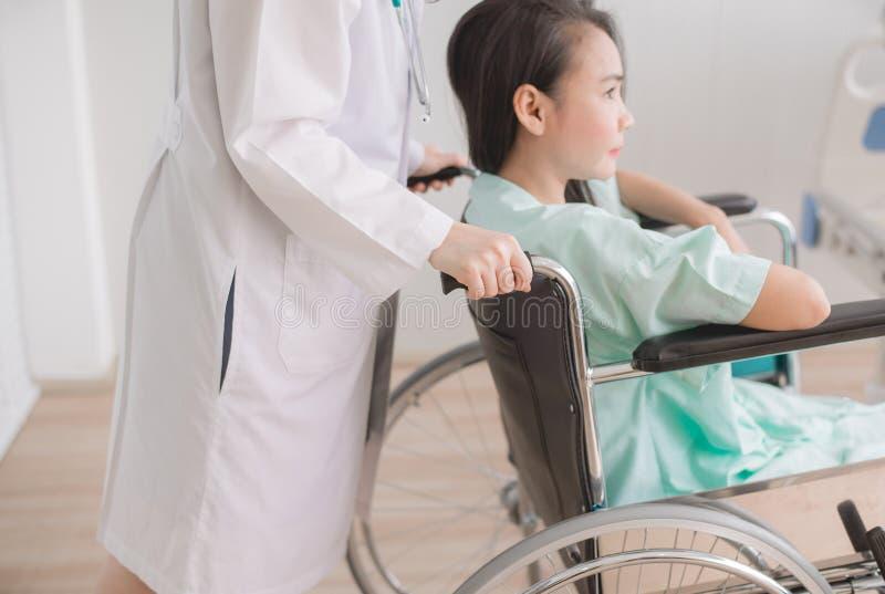 耐心妇女在有站立在手支持后的医生的一个轮椅坐对她 免版税库存照片