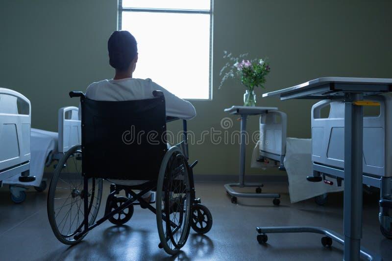 耐心看通过窗口,当坐在轮椅在医院时 免版税库存照片