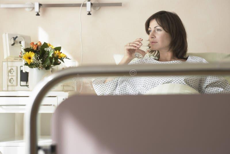 耐心饮用水在医院病床上 免版税库存图片