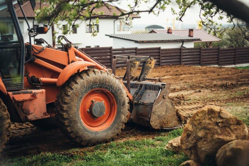 耐用工业推土机环境美化和移动的地球在庭院里 免版税库存图片