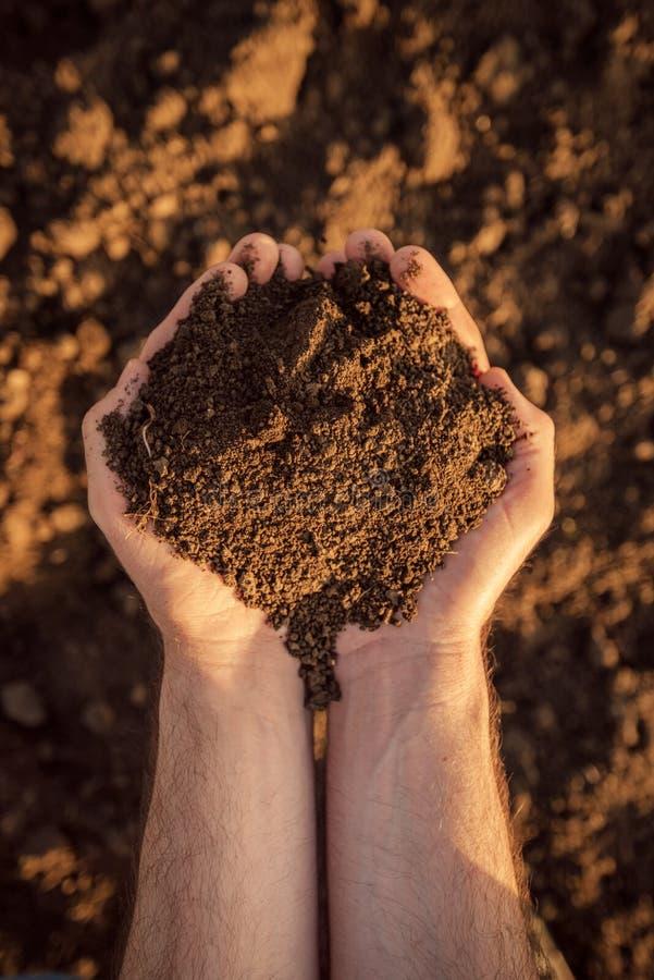 耕地土壤在一位负责任的农夫的手上 免版税库存照片