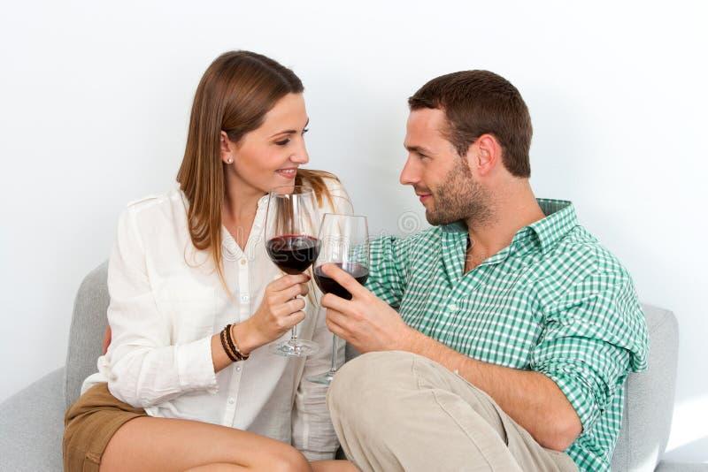 耦合在家享用一杯红葡萄酒。 免版税库存照片