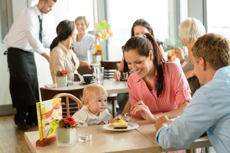 耦合提供他们的儿童蛋糕在咖啡馆 免版税库存图片